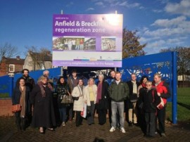 Group photo under the regeneration sign.