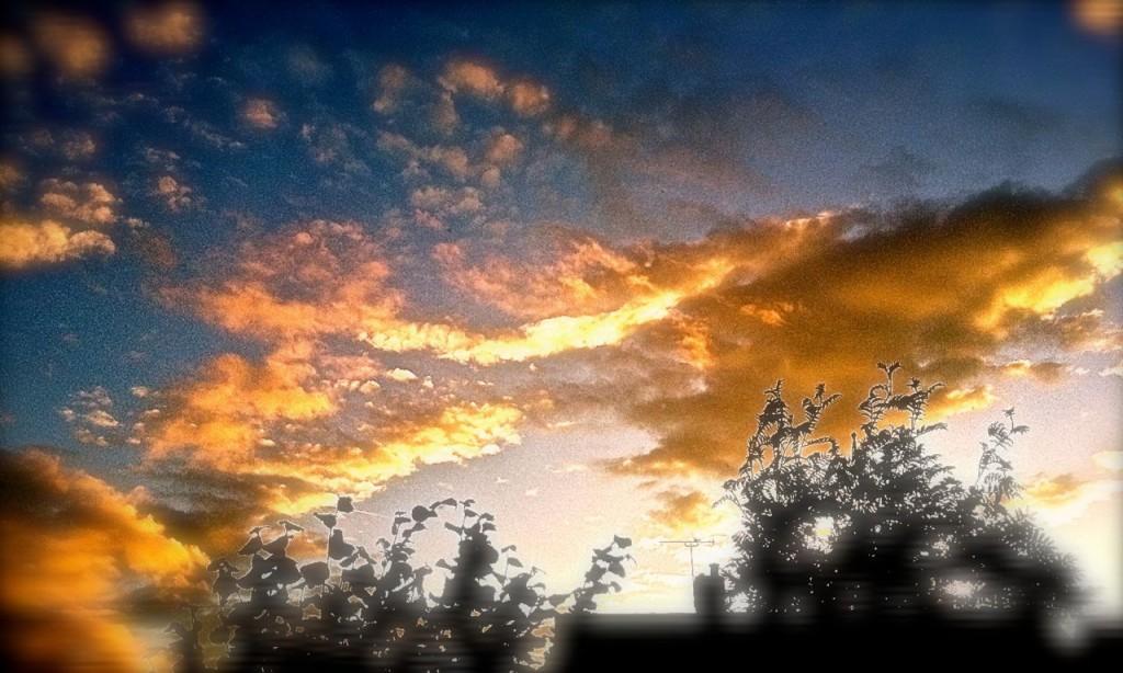 sun setting over a house