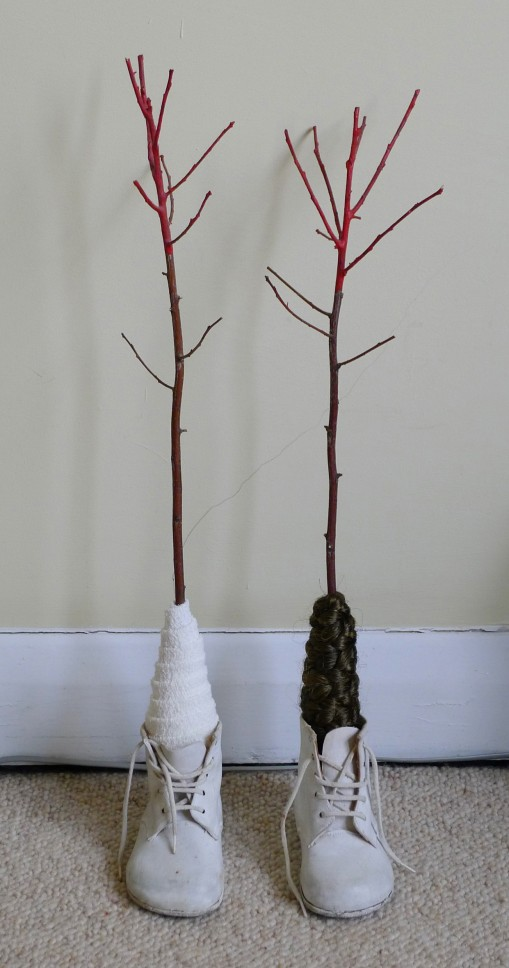 Work-in-process, 2014 Materials: Children's shoes, painted twigs, wool, hair, bandage