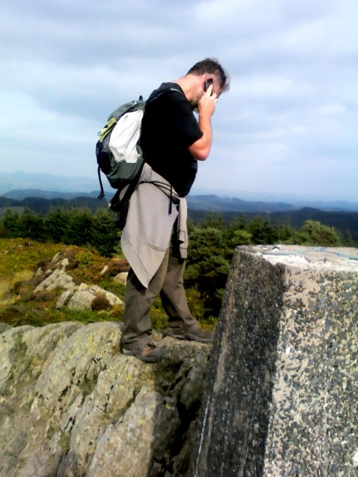 andrew speaking into a mobile phone near to a trig point