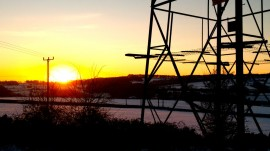 electricity pylon in snow covered field at sun set