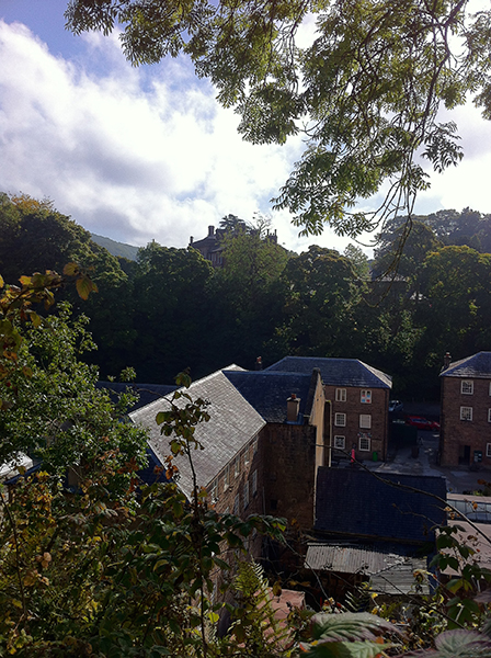 View onto part of Cromford Mills, with Rock House, Richard Arkwright's house, visible through the trees on the rock behind.