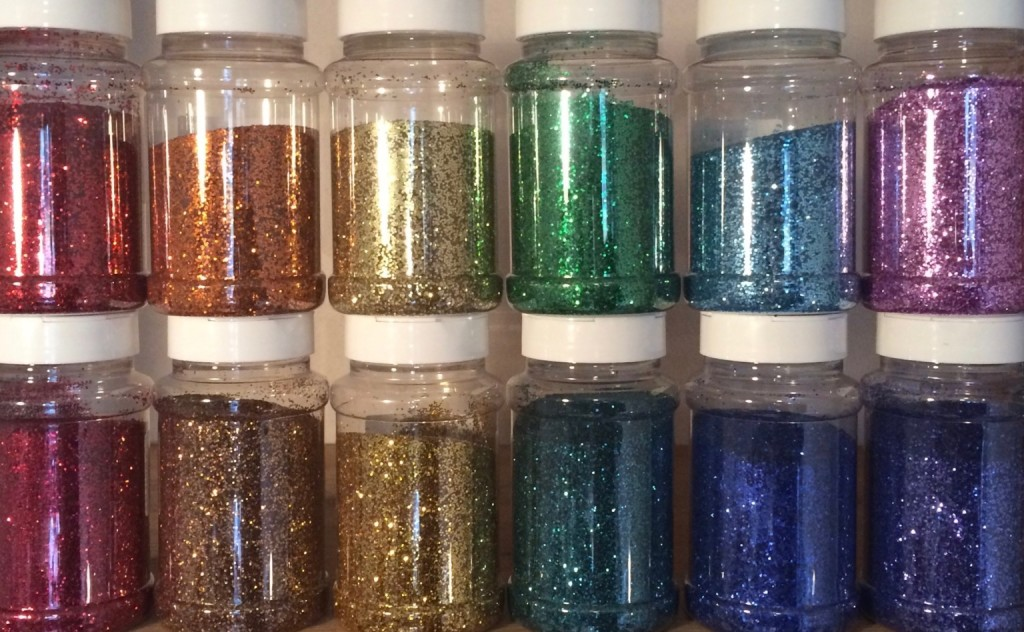 The art work by Stuart Mayes made from 12 plastic jars with lids. Each jar is filled with different coloured glitter including red, orange, yellow, green, indigo, violet, pink and turquoise.
