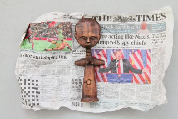 Charlie McConaghy, wooden fertility doll, part of Charlie McConaghy's personal collection, in front of its newspaper wrapping