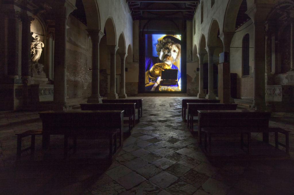 A film projection in a church. The film features a person dressed in a baroque outfit.