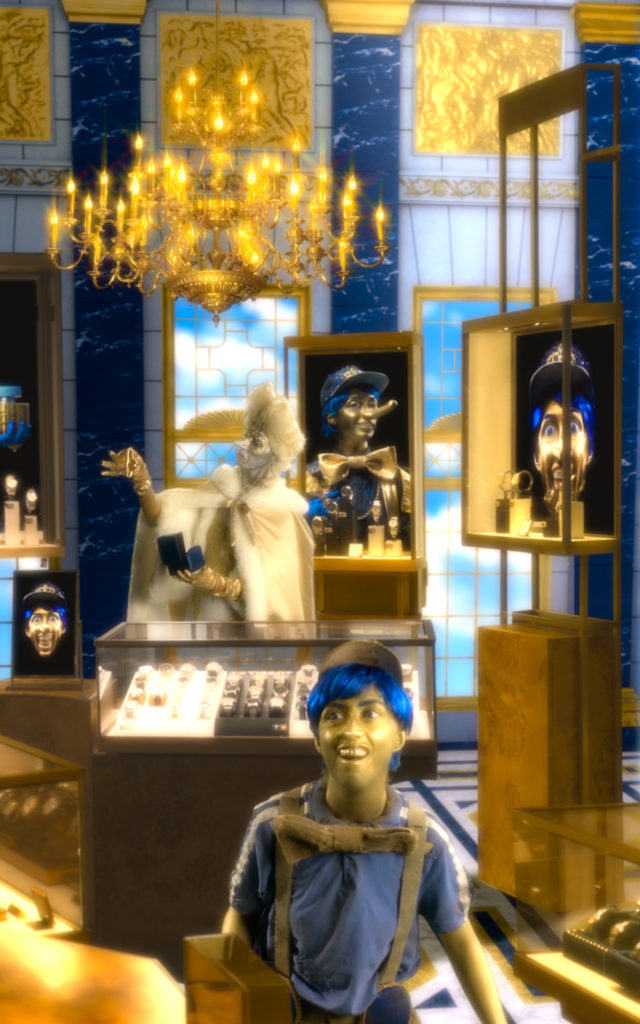 A smiling person with blue hair and a gold face is seen in a baroque looking jewellery shop. To the back of the scene, another person dressed all in white holds up a watch, as if to inspect it.