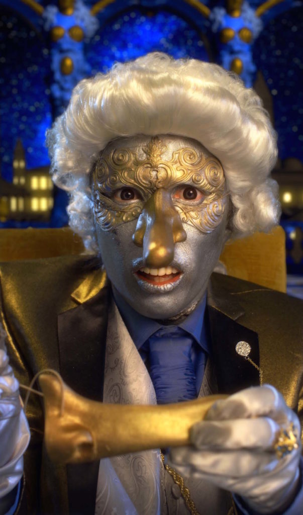 Close up of a silver face wearing a golden Pinnocchio mask.