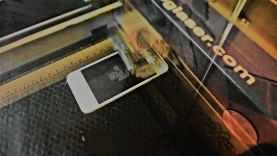 Image of a mobile phone being etched by a laser
