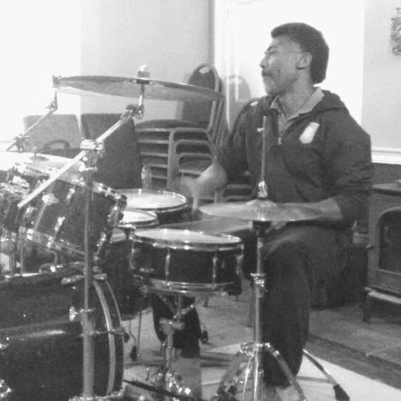 drum kit with man sitting to the right