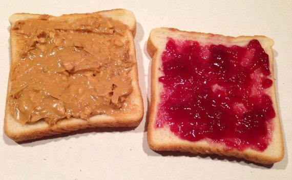 slice of peanut butter on bread on the left and a jammy one on the right