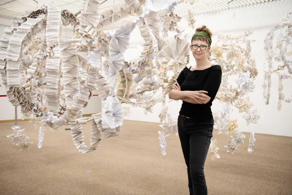 Portrait of Anna Berry in front of a sculptural work made from concertinaed paper