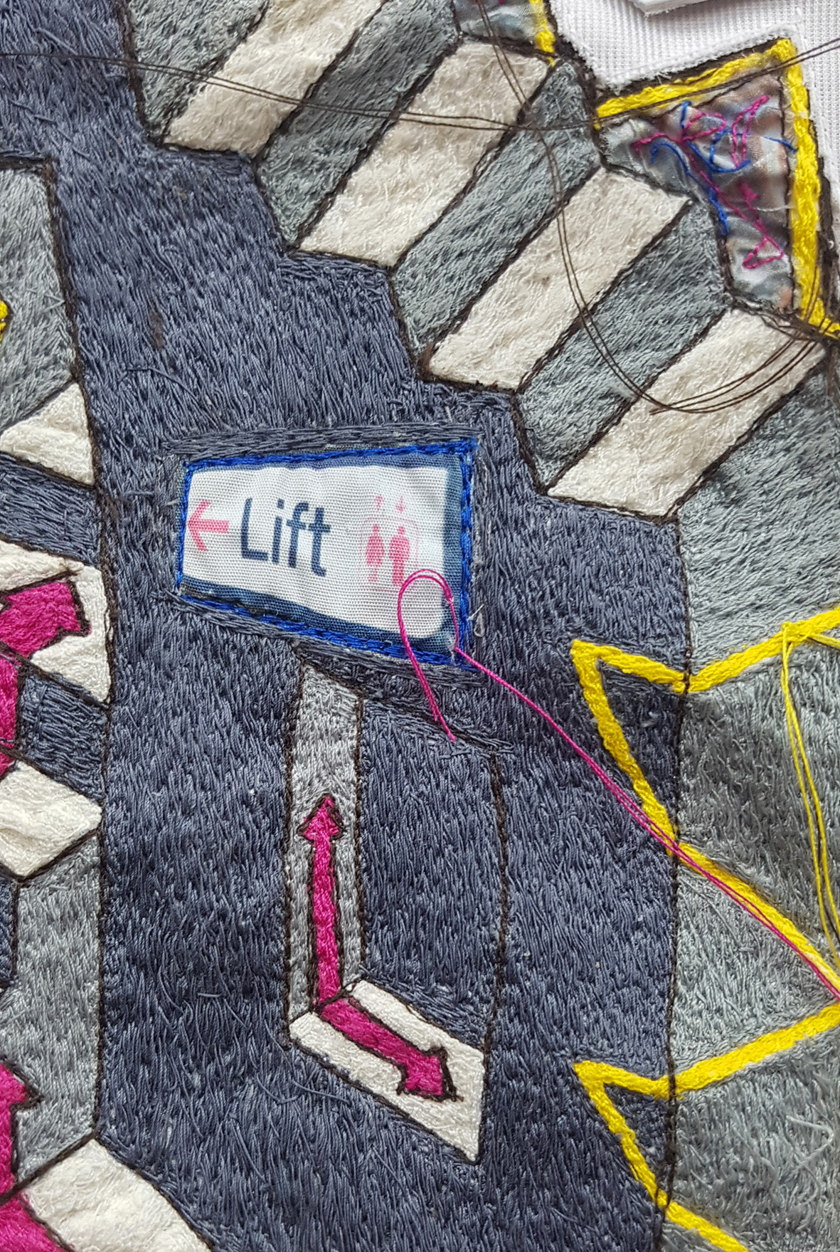 Textile embroidery with abstracted steps and road signage
