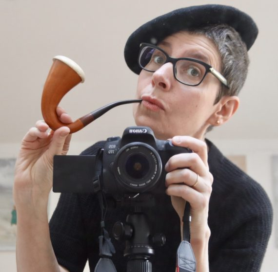 Woman with short are hair and dark framed glasses holding a curly tobacco pipe and wearing a black beret.