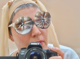 Woman with sheer tights on her head and cut out photos of tomatoes stuck on her glasses posing with a camera.