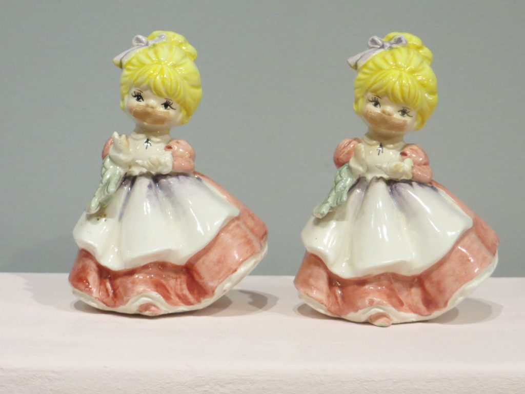 A sculpture by Kate Murdoch made from two identical ceramic figurines wearing pink, full length, dresses with white aprons. The figurines have yellow hair and carry posies of flowers. Sticking plasters have been attached to their mouths.