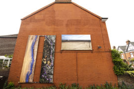 Large photographs on canvas hung on the side of a house.