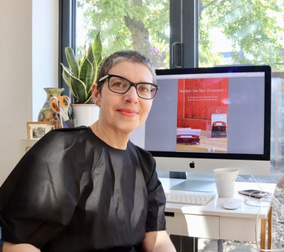 woman with very short grey hair in a black dress in front of an iMac