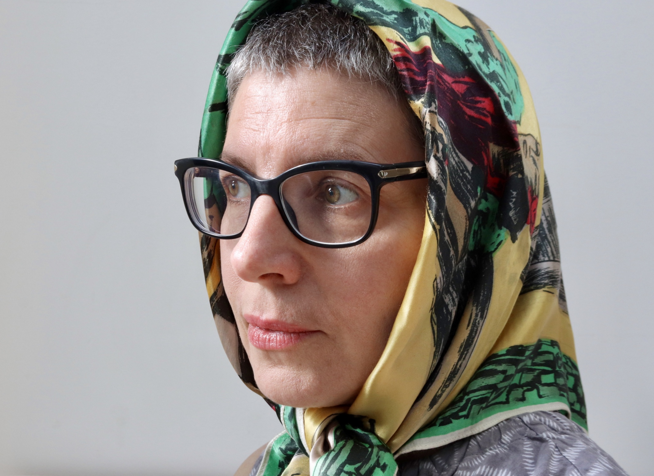 Woman in colourful headscarf and black rimmed glasses