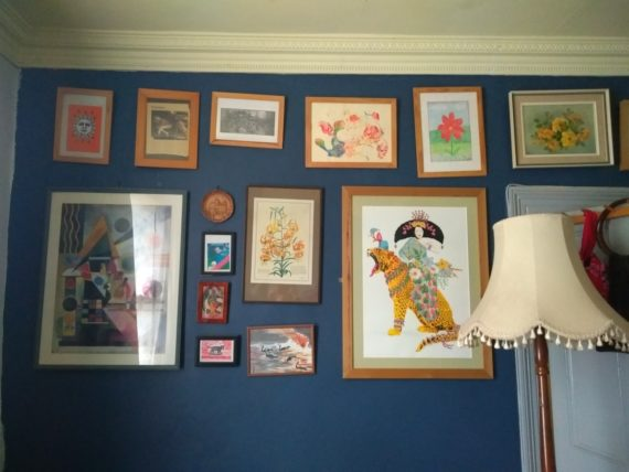 Dark blue wall with a lampshade and collection of artworks