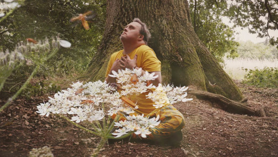 Young white man in a yellow top crouching behind white flowers in a wood, clutching his chest and looking at the sky