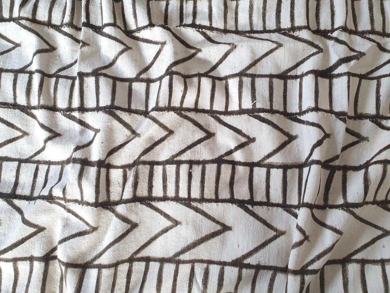 Photo of a piece of mud cloth with alternating rows of directional arrows to the right and vertical stripes