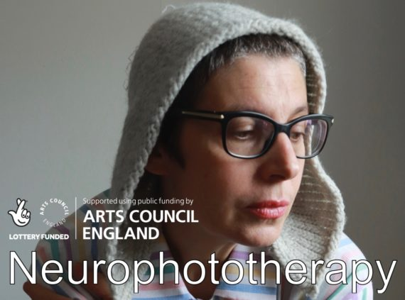 Middle aged white woman wearing cream coloured pollen hood and black rimmed glasses and pastel striped pyjamas.