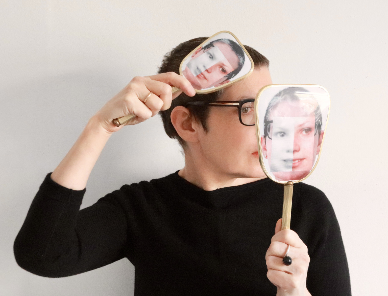 Sonia Boue wearing a black jumper brushing her hair and looking in a small handheld vanity mirror. Both brush and mirror are collaged with photographs of Boue's face.