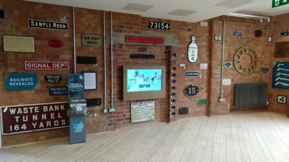 installation view of non linear work surrounded by wall mounted railway artefacts