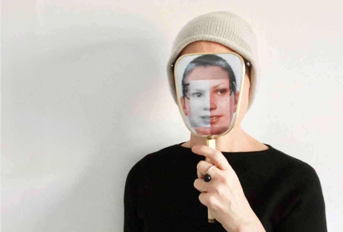 Head and shoulders shot of Sonia Boue as an adult, holding a vanity mirror over her face. The back of the mirror has been collagaed with spliced photographs of Sonia's face as an adult and child.