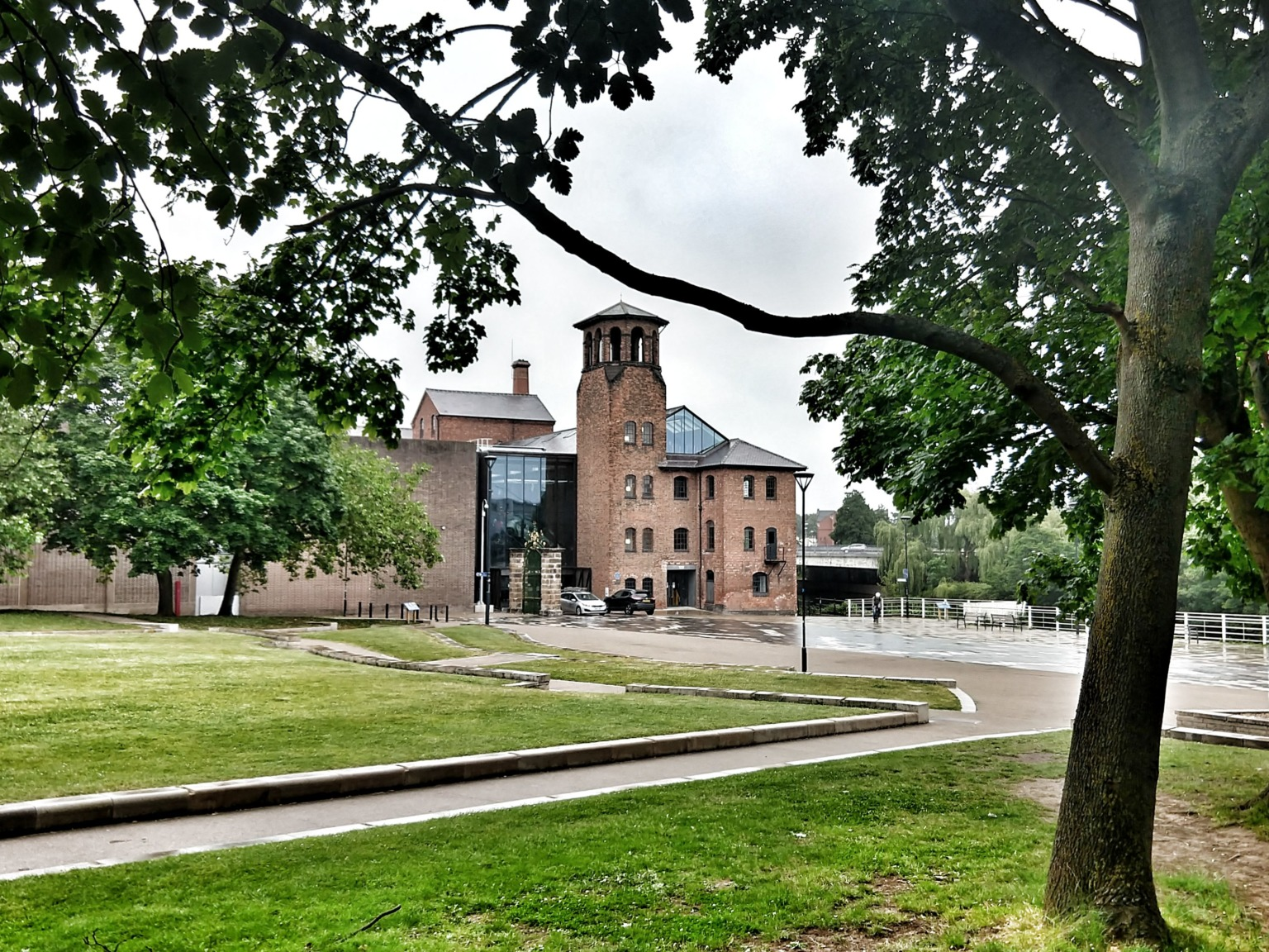 view of the front of the museum of making at derby silk mill framed by tress