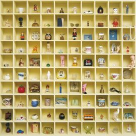 Art work made from a square, modular shelving unit which is yellow in colour. The shelving unit is divided into ten rows along and ten rows up to create 100 small, square, display spaces. Ornaments and other small objects are displayed in each of these spaces.