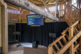 Installation view of a multimedia art work. A TV with text is suspended above speakers. The text is too far away to be legible.