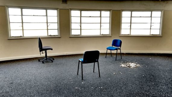 2 meetings chairs and an office swivel chair arranged in a triangle in fron of three windows in a beige wall