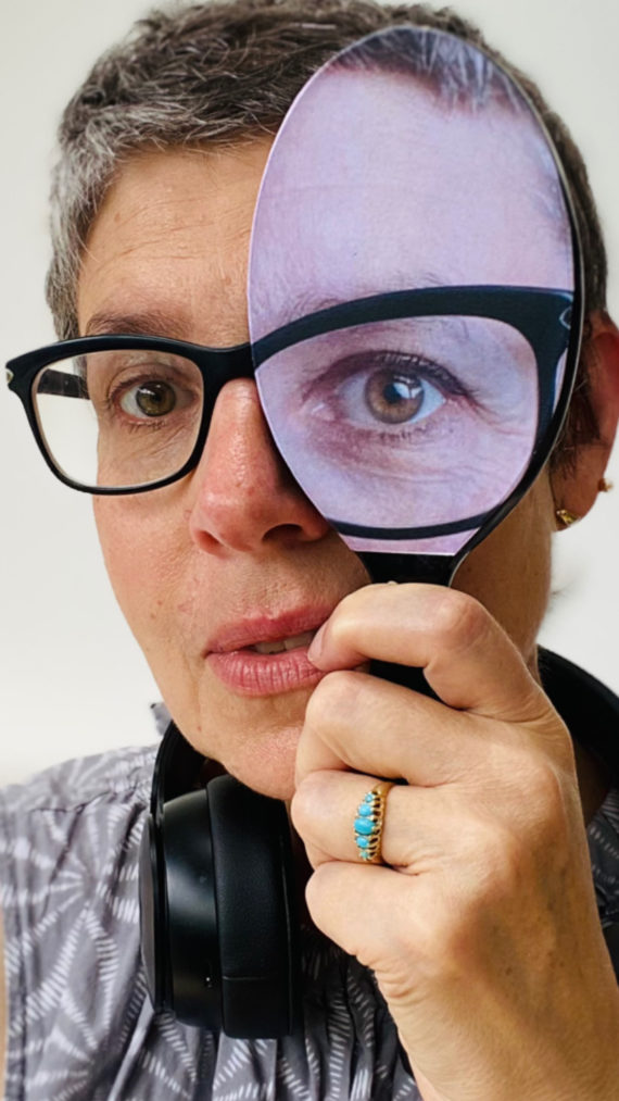 Sonia Boue is a white woman wearing black rimmed glasses and holding a vanity mirror with a collaged eye on it over her left eye. She has closely cropped hair and is wearing black headphones round her neck.