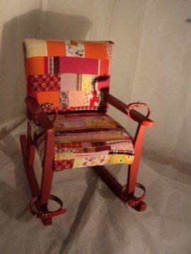 Art work made from an upholstered rocking chair. The seat and back of the chair is covered in a patchwork of coloured fabric. The arms and front legs of the rocking chair have been fitted with safety straps made from brown leather.
