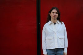 Portrait of Hannah Wallis standing against a red wall.