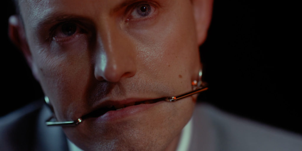 Close-cropped image of a person's face. The person is gripping a metal apparatus held between their teeth.