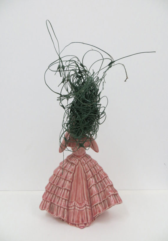A sculpture that includes a ceramic figurine wearing a pink, full length, layered dress. The figurine has green string messily knotted and balled around its head.