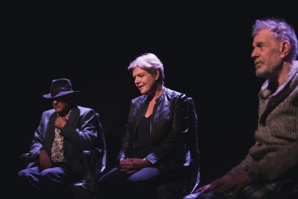 Three seated figures in a dark space. The person on the left wears a suit and dark trilby hat. The person in the centre has short blonde hair, is gazing down and wears a black leather jacket. The person on the right has short grey hair and wears a beige jumper.