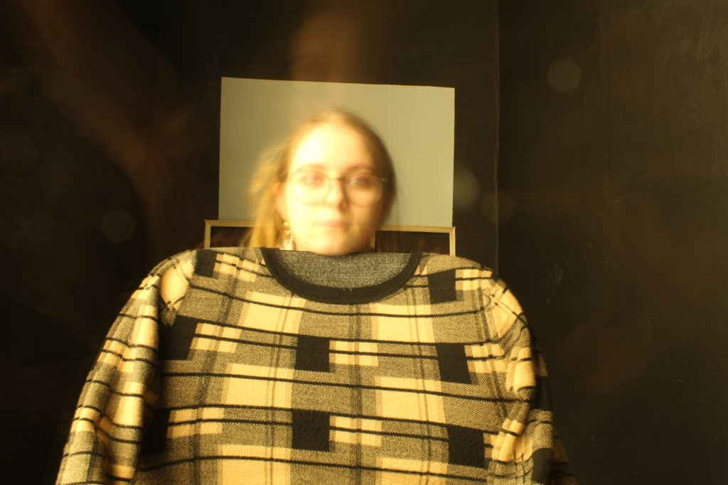 A head peeps out from a horizontal frame which is positioned above a yellow, black and grey checked sweater.