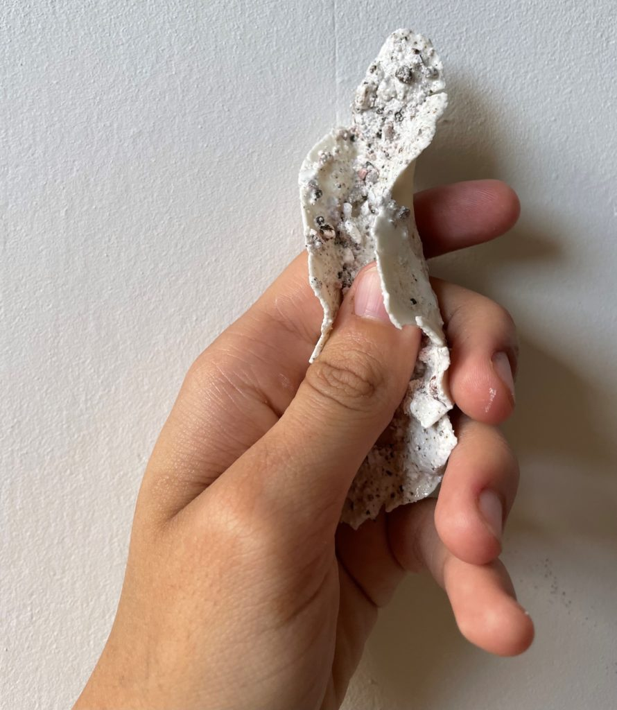 A hand holding part of an art work made from paper clay porcelain and sand with a white stoneware glaze.