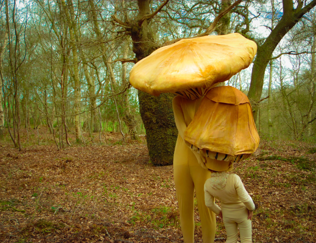 An adult and child dressed in mushroom costumes, standing in the woods.