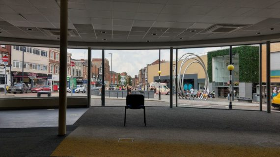 a chair in an empty shop facing a large windown with a view of the spot in derby