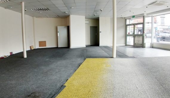 an empty non residential space with a large window on the right hand side.