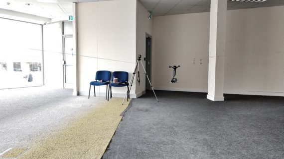 two blue backed chairs against a short white wall in a non residential space.