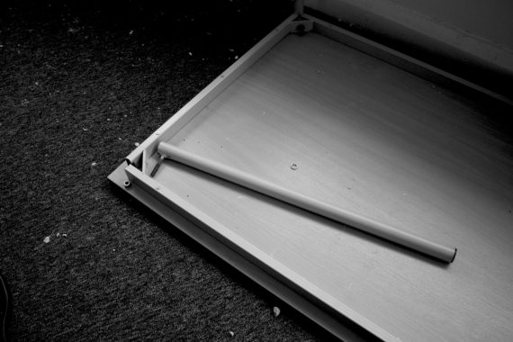 a black and white image of a table top laying top down on carpet with a leg laying next tot he frame and the nut to fix it laying the other side of the frame.