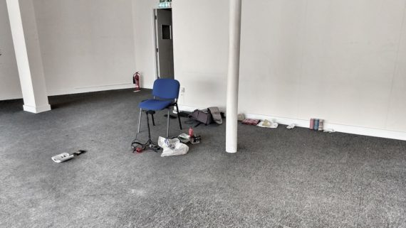 blue chair with stuff on the floor around it against a white wall