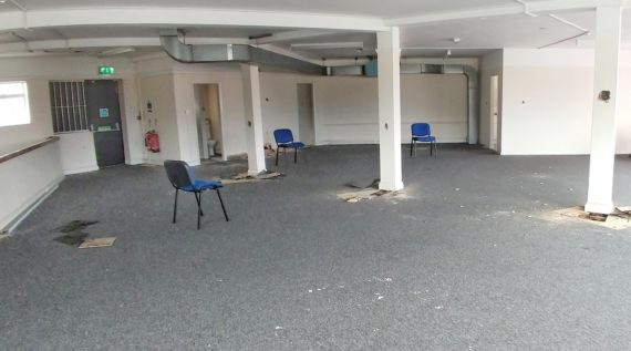 a non residential space with three white columns and three blue backed chairs