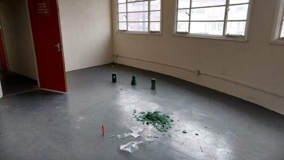 a non residential space with a grey concrete floor with three small geometric green shapes on the floor under multipaned windows