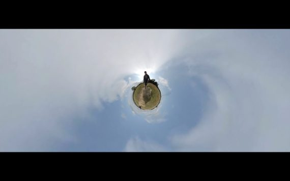 frame grab from a tiny plant 360 video, a person can be seen walking on a green circle surrounded by clouds